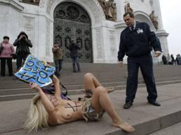 Feministas ucranianas del grupo FEMEN hacen activismo crítico contra el gobierno autoritario ruso frente al templo de Cristo Salvador en Moscú (la pancarta dice: ¡Dios, saca al zar!).